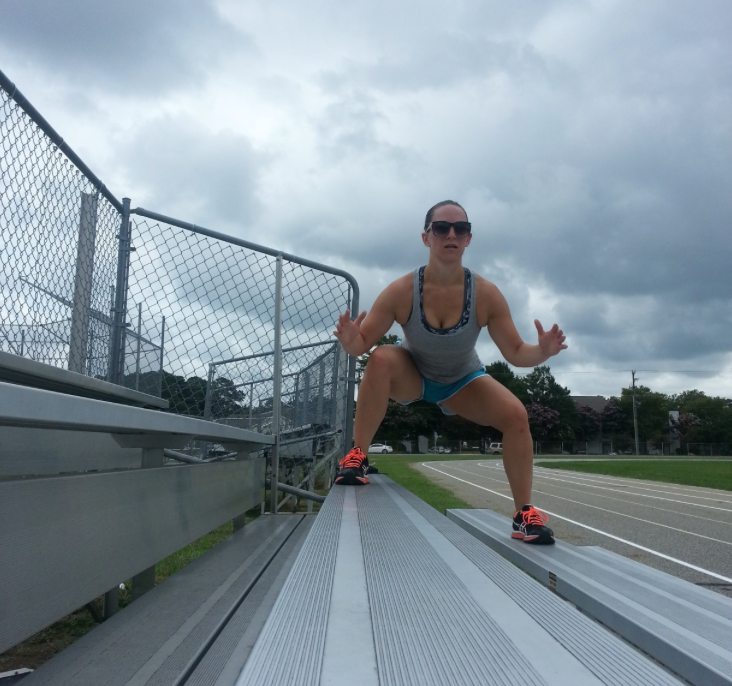 A girl exercising on bleachers.