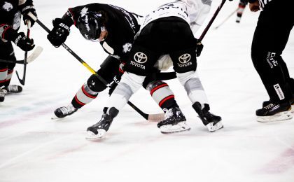 Hockey players using upper body strength during a face off